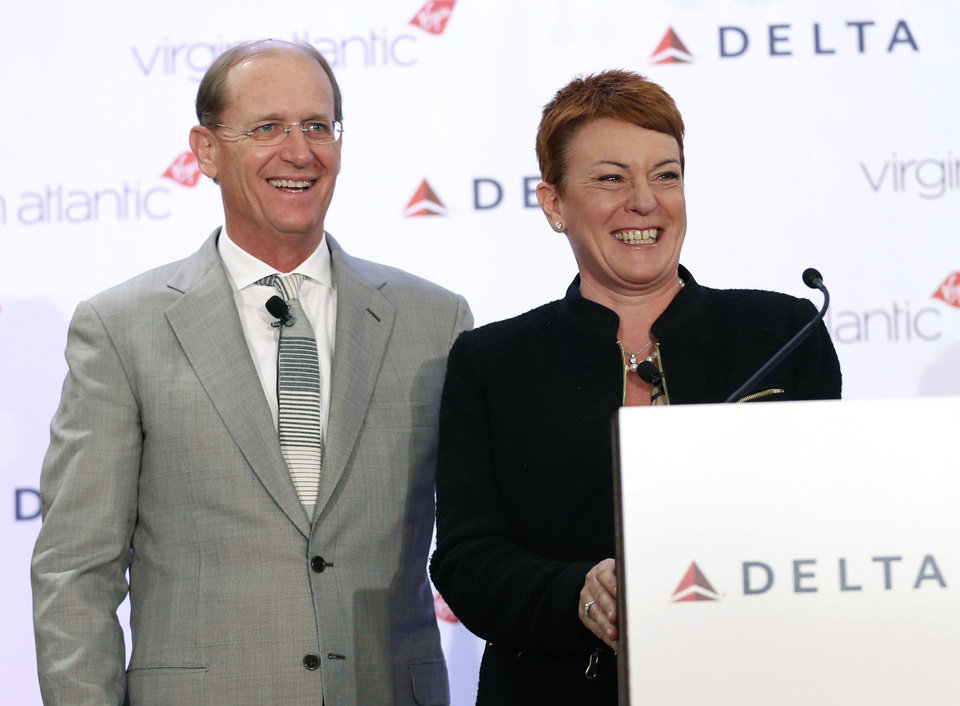 Photo - Delta Airlines CEO Richard Anderson and  Virgin Atlantic CCO Julie Southern laugh during a news conference in New York, Tuesday, Dec. 11, 2012. Delta Air Lines said it will buy almost half of Virgin Atlantic for $360 million as it tries to catch up to rivals in the lucrative New York-to-London travel market. (AP Photo/Seth Wenig)