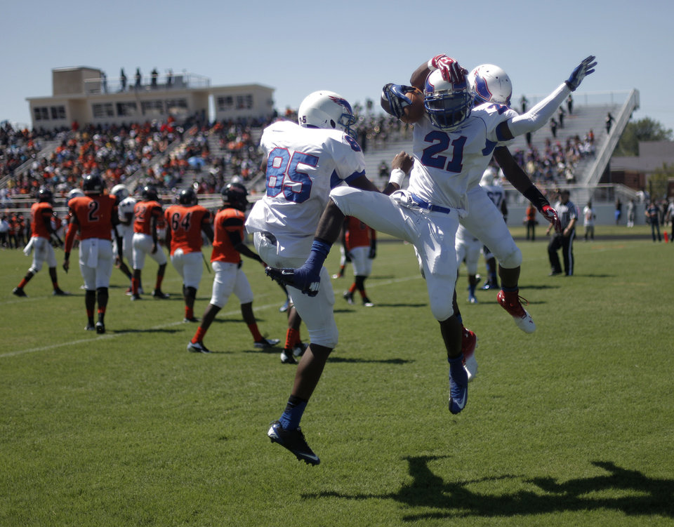 Milwood's Janari Glover (21) celebrates with his teammates, Quincy Dotson (85) and Andre Clanton (22) after scoring a touchdown during a high school football game between Douglass and Millwood in Oklahoma City, Saturday, Sept. 8, 2012.  Photo by Garett Fisbeck, The Oklahoman