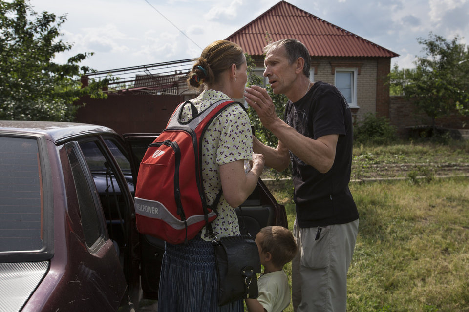 Photo - Olga Mikhailova, left, and her husband Vladimir Mikhailov kiss before abandoning their home with their children in Slovyansk, Ukraine, Wednesday, May 28, 2014. Vladimir Mikhailov will stay a few days at home and then plans to join his wife and children. In Slovyansk, a city 90 kilometers (55 miles) north of Donetsk which has seen repeated clashes over the past few weeks, with residential areas coming under mortar attack Wednesday from government forces. A school was badly damaged and other buildings were hit, according to residents, Wednesday, who told The Associated Press that several people were wounded.(AP Photo/Alexander Zemlianichenko)