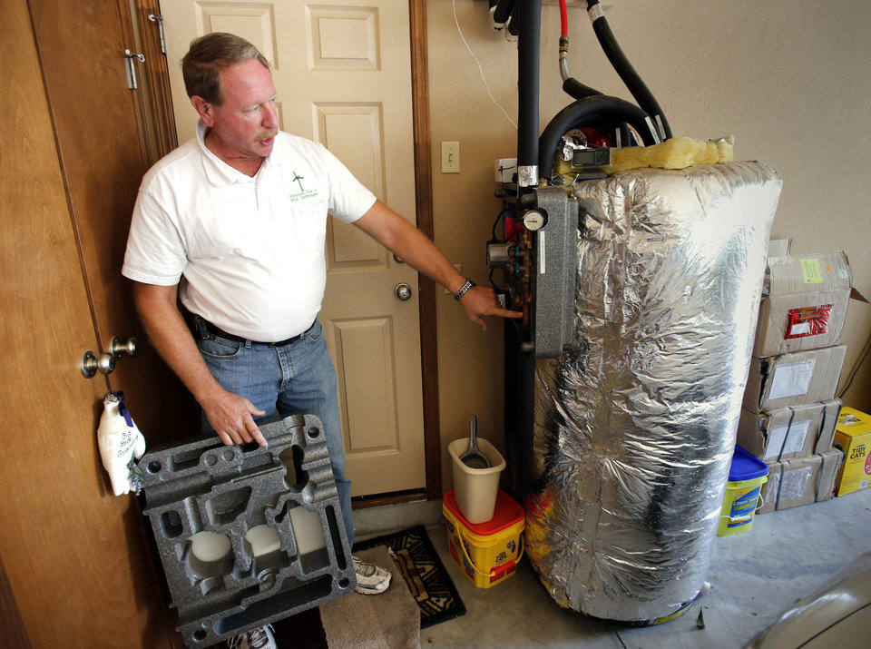 Photo - Choctaw resident Jim Stober shows alternative energy sources Wednesday, including a solar water heating system at his home.  Photo by Steve Sisney, The Oklahoman