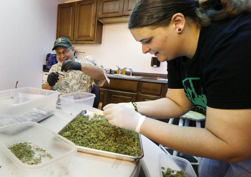 Photo - In this photo taken July 1, 2014, workers Kristi Tobias, right, and Bruce Cumming prepare packets of a variety of recreational marijuana named