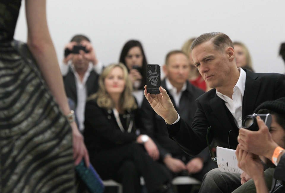 Bryan Adams takes a photograph of a model wearing a design created by Vivienne Westwood during London Fashion Week, at the Saatchi Gallery in West London, Sunday, Feb. 17, 2013. (Photo by Joel Ryan/Invision/AP) ORG XMIT: JRLON111