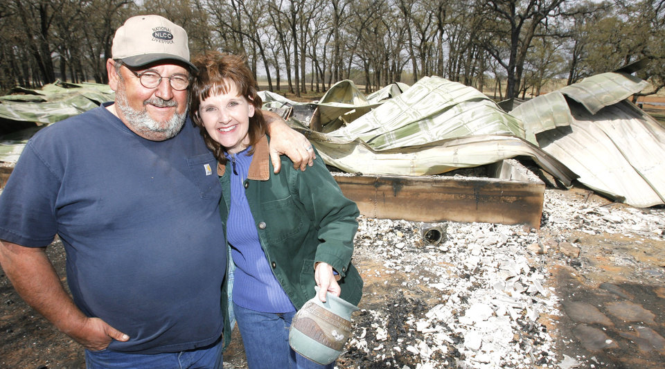 Left: Jerry and Tammy England stand in front of their log cabin that burned in a fire Thursday in McClain County.  Photo BY  DAVID MCDANIEL, THE OKLAHOMAN