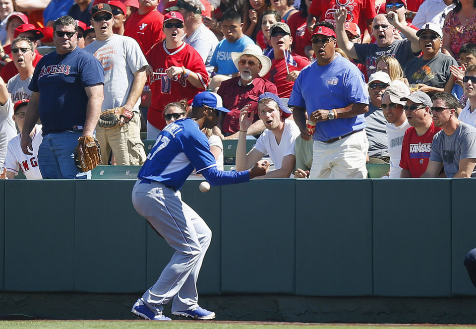 Photo - Kansas City Royals' Justin Maxwell drops a foul ball hit by Los Angeles Angels' Mike Trout during the second inning of an exhibition spring training baseball game on Friday, March 21, 2014, in Tempe, Ariz. (AP Photo/Ross D. Franklin)