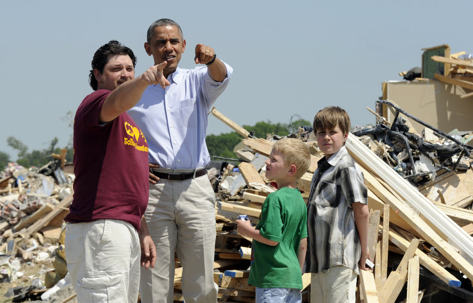 Photo - President Barack Obama tours tornado-damaged areas of Vilonia, Ark., Wednesday, May 7, 2014 and talks with Daniel Smith and his sons Garrison Dority and Gabriel Dority, right. Obama is visiting with first responders and families affected by the recent tornados before traveling on to California where he will raise money for the Democratic Party and receive an award from a foundation created by movie director Steven Spielberg. (AP Photo/Susan Walsh)