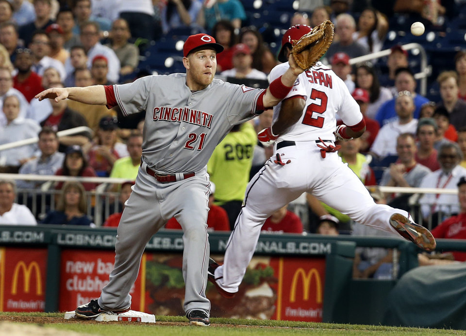 Photo - Cincinnati Reds first baseman Todd Frazier (21) can't catch the throw as Washington Nationals' Denard Span (2) is safe at first, and continues to third base during the third inning of a baseball game at Nationals Park on Tuesday, May 20, 2014, in Washington. (AP Photo/Alex Brandon)