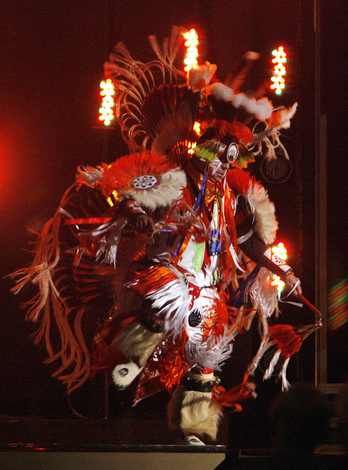 Photo - A Native American dancer performs during the 'Flames Burns On' during the Centennial Spectacular to celebrate the 100th birthday of the State of Oklahoma at the Ford Center on Friday, Nov. 16, 2007, in Oklahoma City, Okla. Photo By CHRIS LANDSBERGER, The Oklahoman
