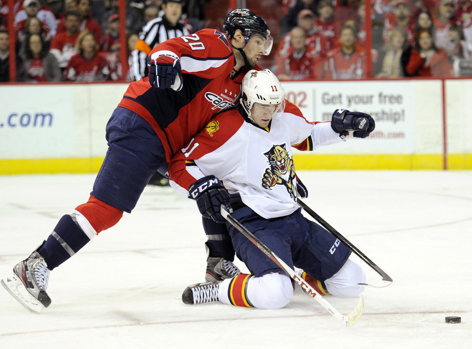 Washington Capitals right wing Troy Brouwer (20) fights for the puck against Florida Panthers center Jonathan Huberdeau (11) during the second period of an NHL hockey game, Saturday, Feb. 9, 2013, in Washington. (AP Photo/Nick Wass)