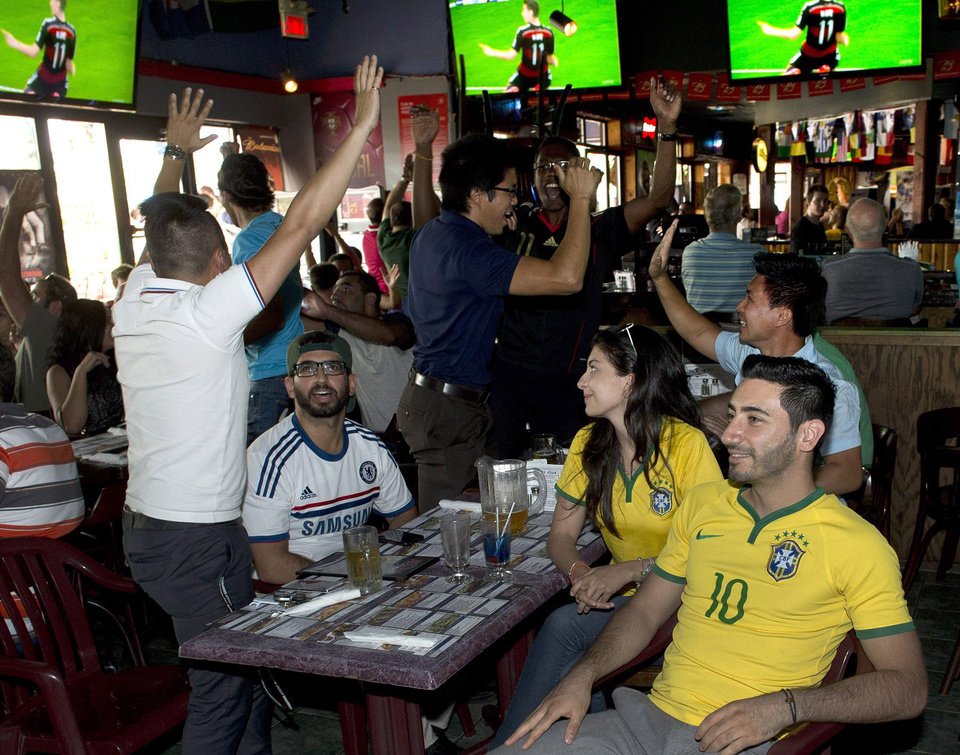 Photo - Fans react after the second German goal as they watch the Germany-Brazil World Cup soccer semi-final at PJ's Pub on July 8, 2014 in Montreal.  Canada has not sent a team to the World Cup in a generation. But that hasn't stopped Canadians from going a little Cup crazy. FIFA organizers say Canadians bought more than 29,000 tickets to World Cup matches, outranking all other nations that didn't qualify for the Cup and behind only 10 nations that did. (AP Photo/The Canadian Press, Ryan Remiorz)