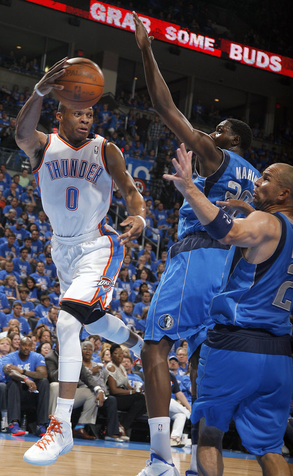 Oklahoma City's Russell Westbrook (0) passes the ball as Ian Mahinmi (28) and Dallas' Jason Kidd (2) during game one of the first round in the NBA playoffs between the Oklahoma City Thunder and the Dallas Mavericks at Chesapeake Energy Arena in Oklahoma City, Saturday, April 28, 2012. Photo by Sarah Phipps, The Oklahoman