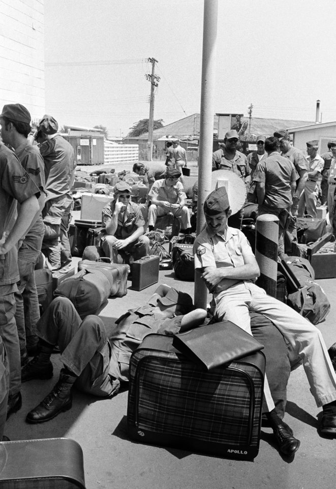 Photo - In this March 27, 1973 photo, an American GI takes a nap atop his luggage as he and other troops wait to begin out processing at Camp Alpha in Saigon, as withdrawal of U.S. troops resume after a 10-day dispute over POWs.  All U.S. troops are due out Thursday. As the last U.S. combat troops left Vietnam 40 years ago, angry protesters still awaited them at home. North Vietnamese soldiers took heart from their foes' departure, and South Vietnamese who had helped the Americans feared for the future. While the fall of Saigon two years later — with its indelible images of frantic helicopter evacuations — is remembered as the final day of the Vietnam War, Friday marks an anniversary that holds greater meaning for many who fought, protested or otherwise lived it. (AP Photo/Chick Harrity)