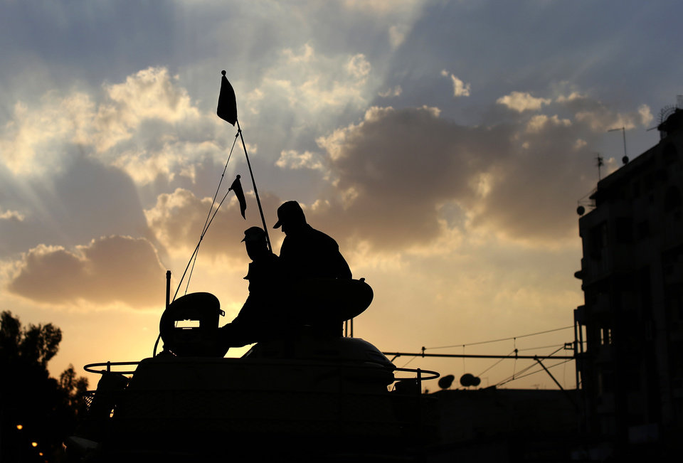 Photo - Egyptian army soldiers sit on top of their tank as the sun sets outside the presidential palace, background, in Cairo, Egypt, Saturday, Dec. 8, 2012. Egypt's military warned Saturday of 'disastrous consequences' if the crisis that sent tens of thousands of protesters back into the streets is not resolved, signaling the army's return to an increasingly polarized and violent political scene.(AP Photo/Hassan Ammar)
