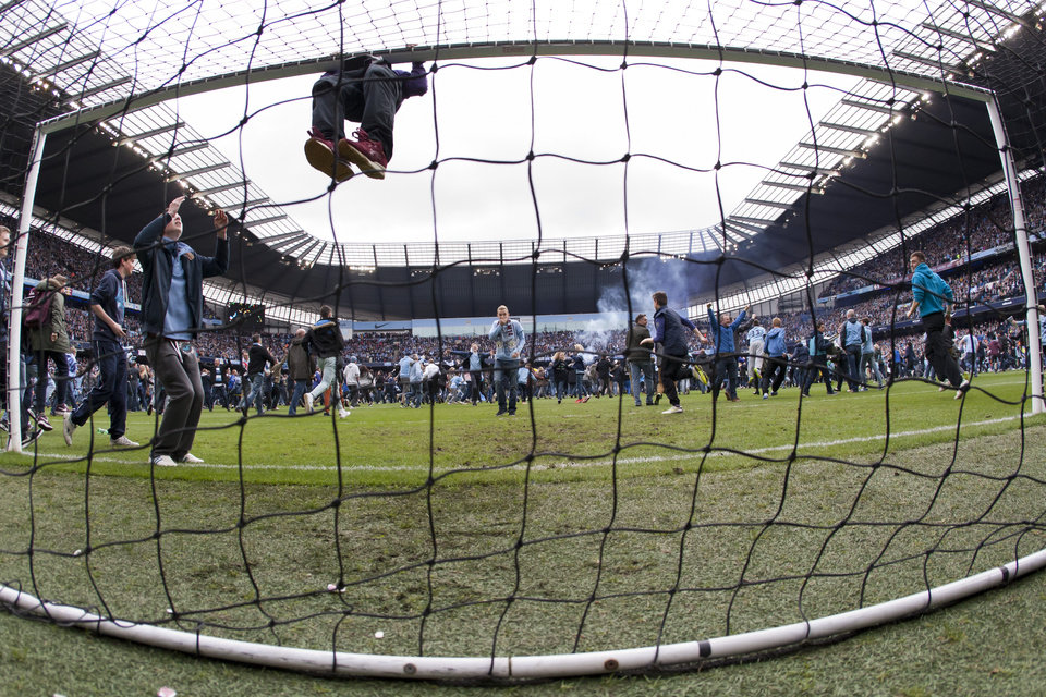 Photo - Manchester City supporters celebrate as their team wins the English Premier League with a 2-0 win against West Ham United in their English Premier League soccer match at the Etihad Stadium in Manchester, England, Sunday May 11, 2014.  (AP Photo/Jon Super)