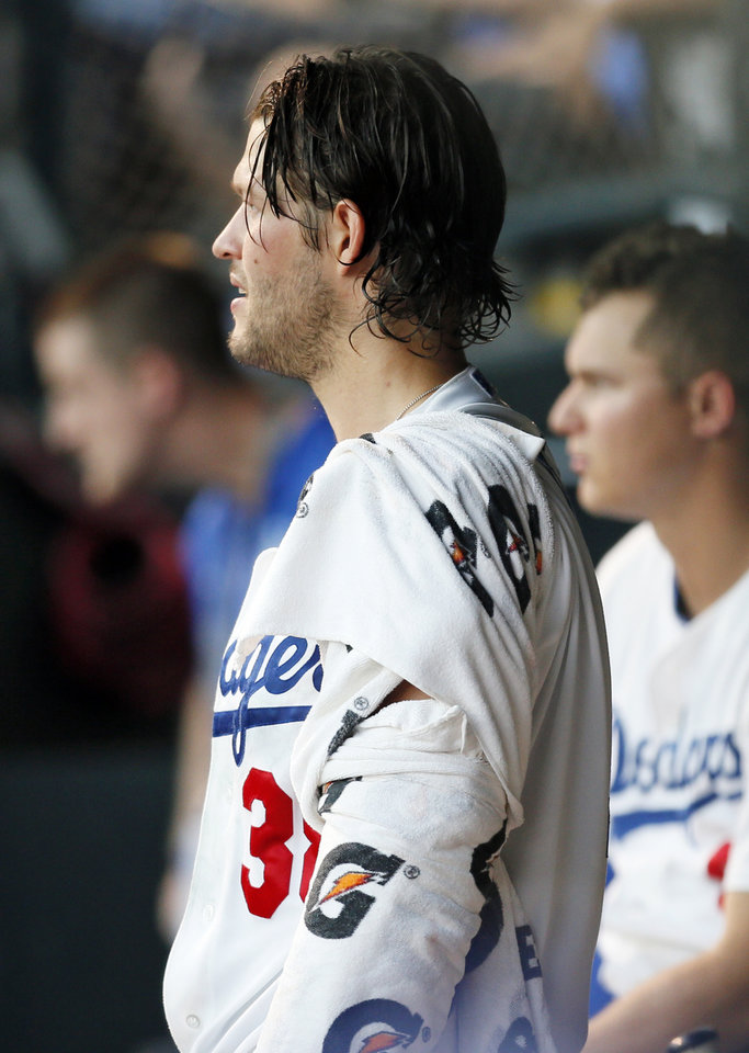 Photo - Clayton Kershaw watches the game in the Oklahoma City dugout during a Triple-A baseball game between the Oklahoma City Dodgers and the Omaha Storm Chasers at the Chickasaw Bricktown Ballpark in Oklahoma City, Saturday, Aug. 26, 2017. The Los Angeles pitcher was on a rehab assignment in Oklahoma City. Photo by Nate Billings, The Oklahoman