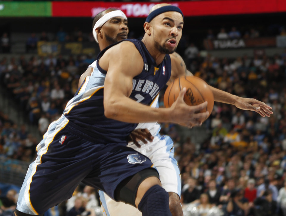 Photo - Memphis Grizzlies guard Jerryd Bayless, front, drives the lane for a shot past Denver Nuggets forward Corey Brewer in the first quarter of an NBA basketball game in Denver, Friday, March 15, 2013. (AP Photo/David Zalubowski)