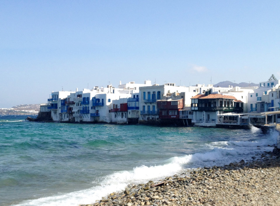 Photo - This July 6, 2014 photo shows homes tucked into the waterfront of the island of Mykonos, in an area known as Little Venice. Mykonos is located in the Cyclades, a Greek island chain in the Aegean Sea. The Cyclades are known for panoramic views of the sea, homes tucked into cliffsides and waterfronts, black-sand beaches and dramatic sunsets. (AP Photo/Kristi Eaton)