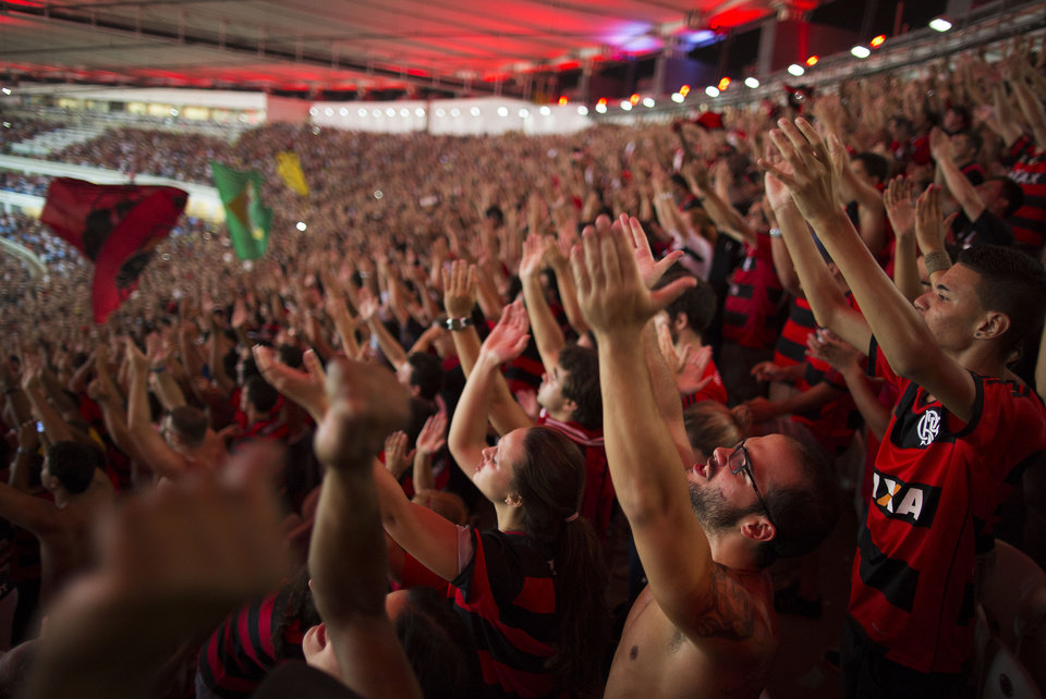Photo - In this April 9, 2014 photo, supporters of the Flamengo soccer team wave their hands during a Copa Libertadores soccer match at Maracana stadium in Rio de Janeiro, Brazil. Soccer's big moment happens in June this year as the best players on the planet meet in Brazil for the World Cup. (AP Photo/Leo Correa)