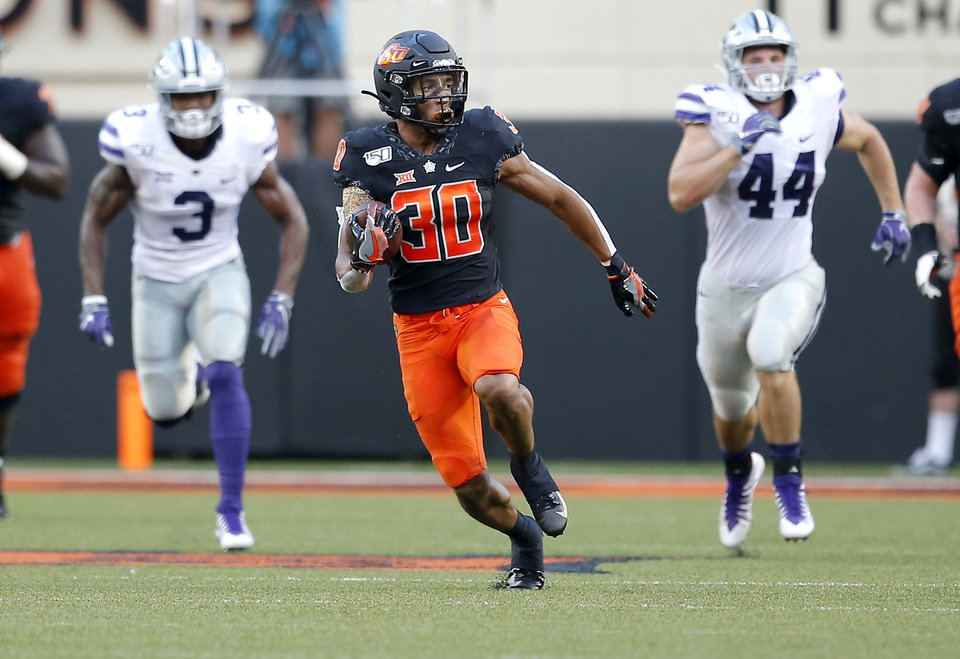 Photo - Oklahoma State's Chuba Hubbard (30) runs for a big gain as Kansas State's Elijah Sullivan (3) and Kyle Ball (44) chase him in the first quarter during the college football game between the Oklahoma State Cowboys and the Kansas State Wildcats at Boone Pickens Stadium in Stillwater, Okla., Friday, Sept. 27, 2019. [Sarah Phipps/The Oklahoman]