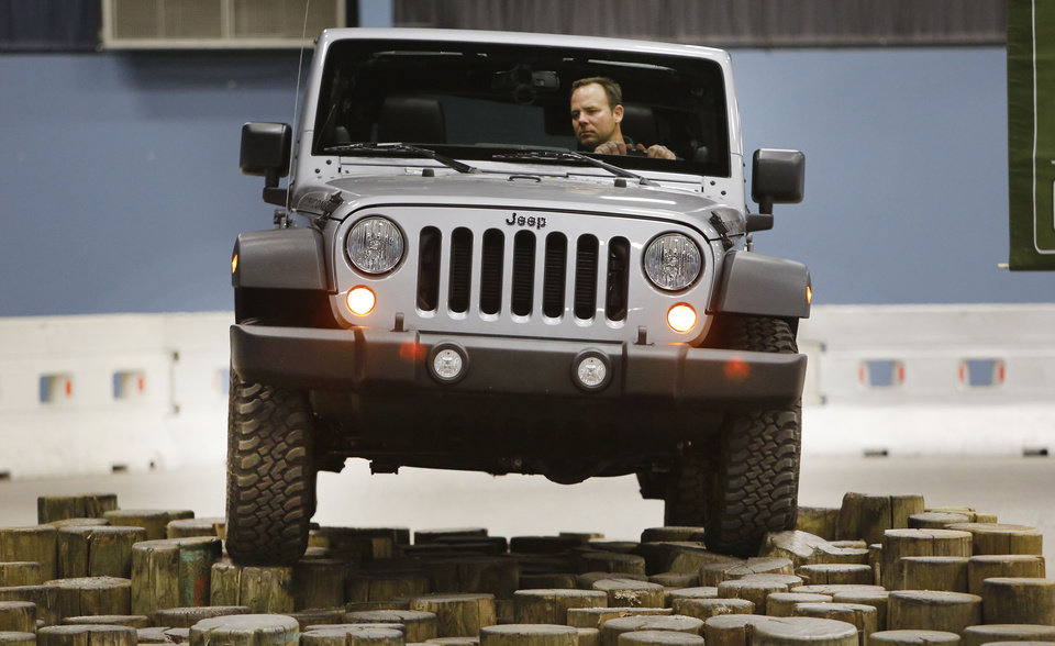 Photo - Visitors can ride along with a professional driver at Camp Jeep, one of the interactive features at the Oklahoma City International Auto Show. Here, Bob Lowe drives a Jeep Wrangler Rubicon through the obstacle course.  Steve Gooch - The Oklahoman