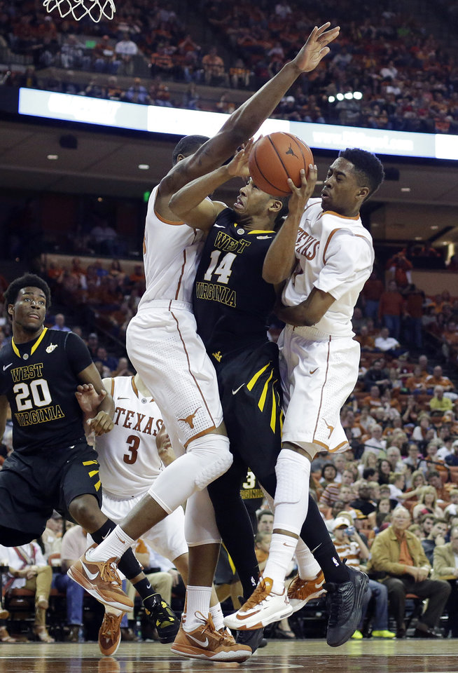 Photo - West Virginia's Gary Browne (14) is presured by Texas' Prince Ibeh, left, and Isaiah Taylor, right, as he tries to score during the second half of an NCAA college basketball game Saturday, Feb. 15, 2014, in Austin, Texas. Texas won 88-71. (AP Photo/Eric Gay)