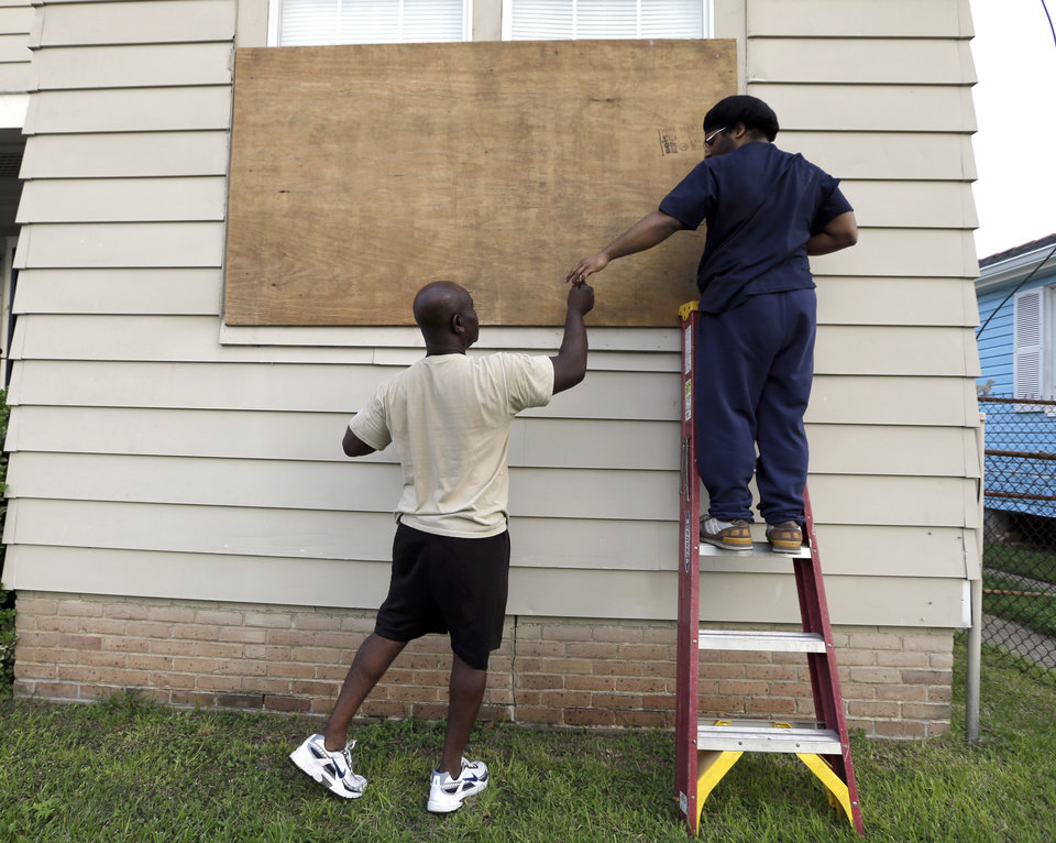 Photo -   Stacey Davis, left, hands a screw to his son as they board up windows on their home before Tropical Storm Isaac hits Tuesday, Aug. 28, 2012, in New Orleans. Tropical Storm Isaac is churning it's way across the Gulf of Mexico towards New Orleans. (AP Photo/David J. Phillip)