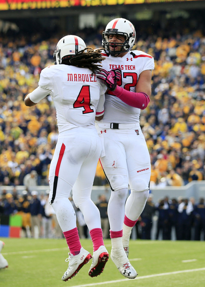 Photo - Texas Tech's Jace Amaro (22) and Bradley Marquez (4) celebrate a touchdown during the third quarter of an NCAA college football game against West Virginia in Morgantown, W.Va., on Saturday, Oct. 19, 2013. Texas Tech won 37-27. (AP Photo/ Christopher Jackson)