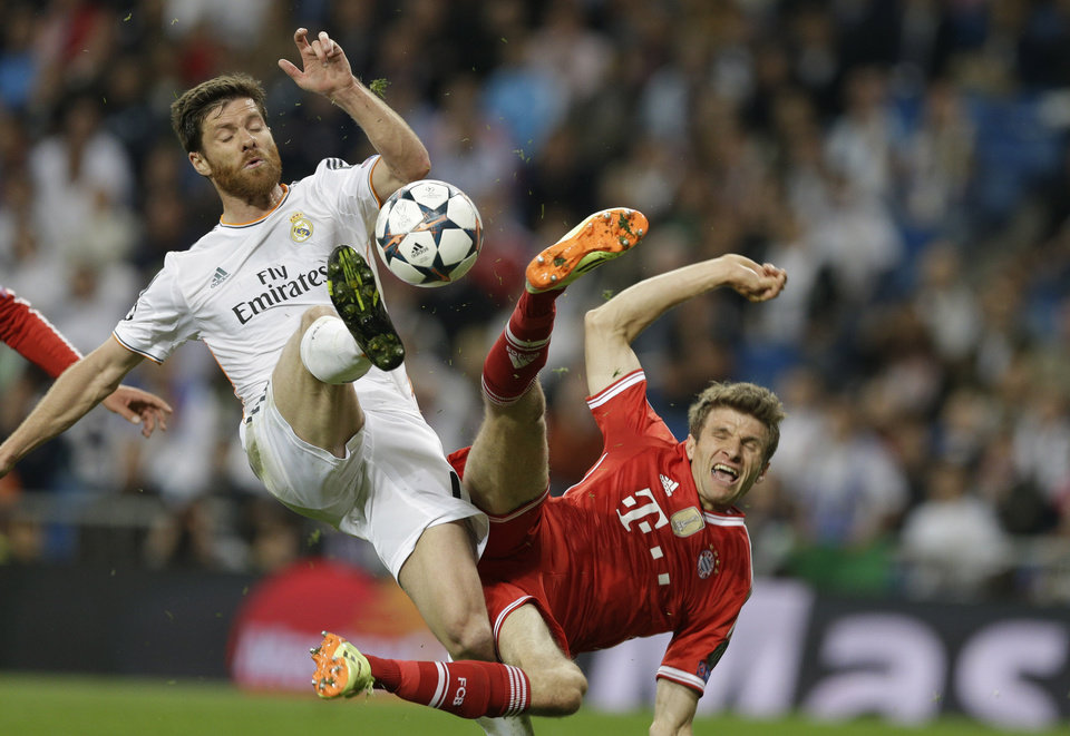 Photo - Real's Xabi Alonso, left, and Bayern's Thomas Mueller challenge for the ball during a  Champions League semifinal first leg soccer match between Real Madrid and Bayern Munich at the Santiago Bernabeu stadium in Madrid, Spain, Wednesday, April 23, 2014 .(AP Photo/Paul White)