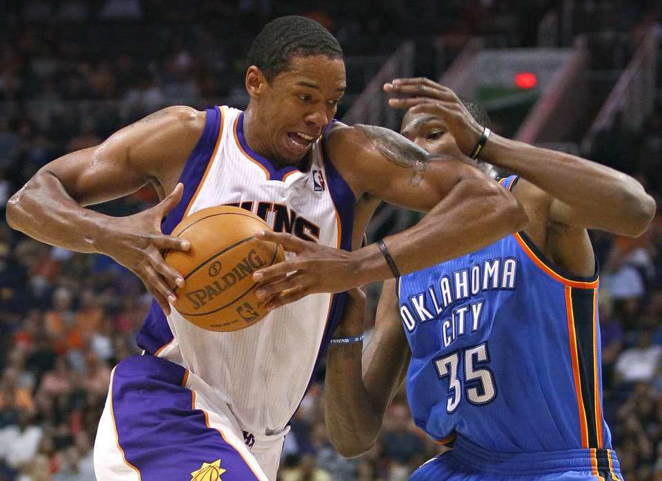 Photo - Phoenix Suns forward Channing Frye drives against Oklahoma City Thunder forward Kevin Durant (35) during the second half of an NBA basketball game, Wednesday, April 18, 2012, in Phoenix. (AP Photo/Matt York)  ORG XMIT: PNU110