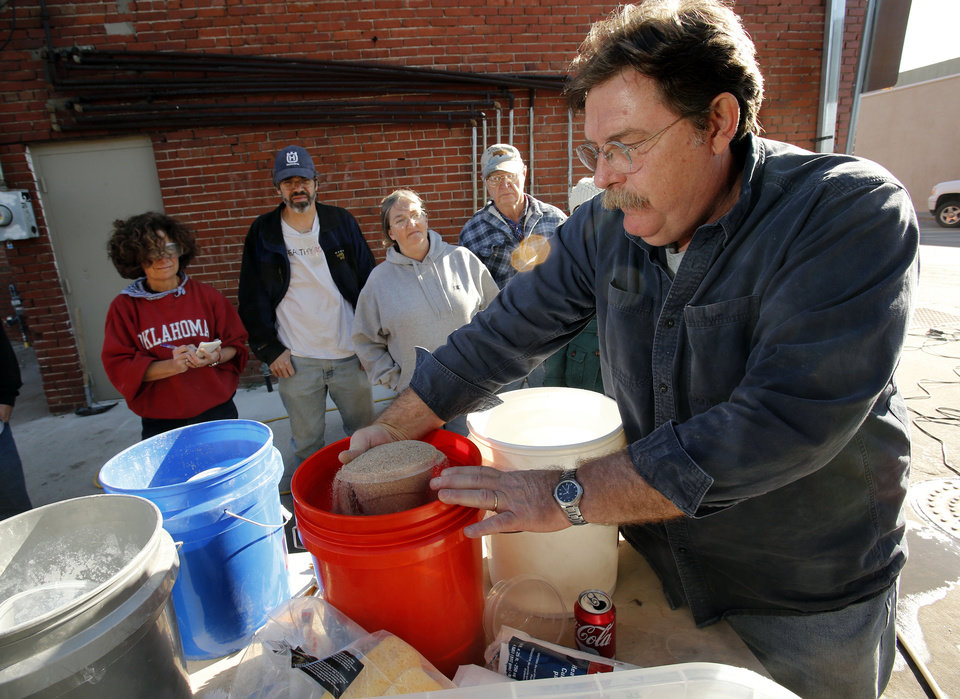 Bob Yapp, a nationally recognized preservation expert, prepares mortar for masonry repairs on a building on E Main Street in Norman  Saturday while workshop participants watch. PHOTO BY STEVE SISNEY, THE OKLAHOMAN <strong>STEVE SISNEY</strong>
