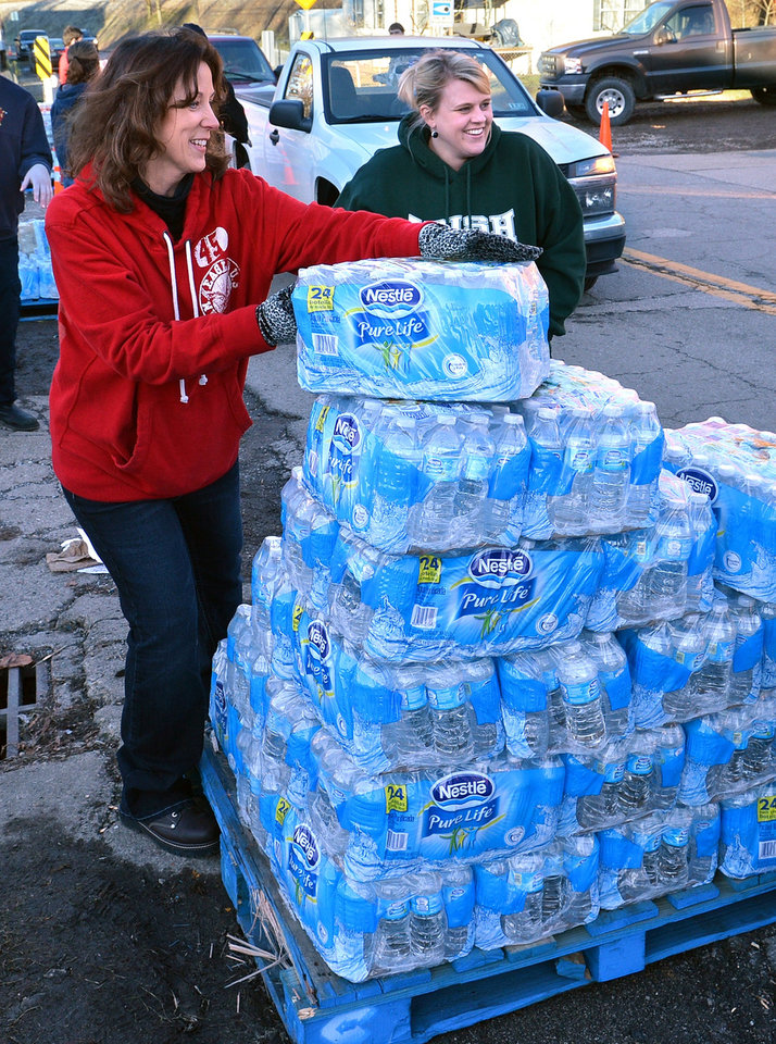 Photo - Christie Peterson, left, and Melissa Appleton pass out cases of water at the Malden Volunteer Fire Department in Malden, W.Va., Sunday Jan. 12, 2014.  The water emergency continues in the Charleston area due to a chemical spill.  (AP Photo/Charleston Daily Mail, Craig Cunningham)