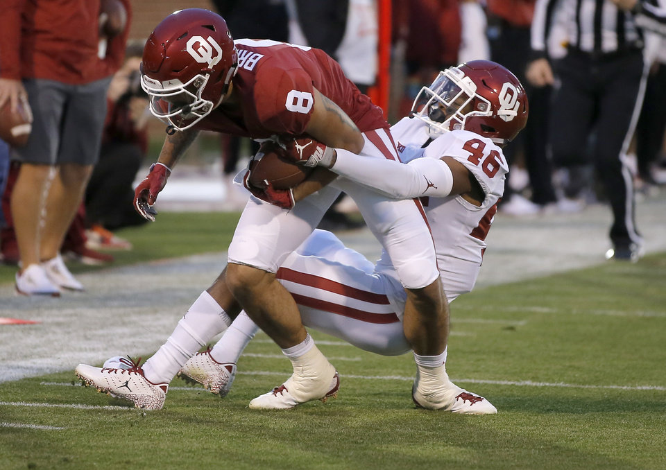 Photo - Oklahoma's Trejan Bridges (8) is brought down by  Robert Charlton (46) during the University of Oklahoma's (OU) spring football game at Gaylord Family-Oklahoma Memorial Stadium in Norman, Okla., Friday, April 12, 2019. Photo by Bryan Terry, The Oklahoman