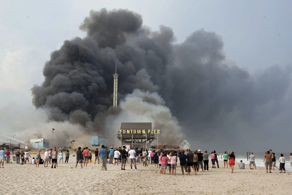 Onlookers watch from the shore as black smoke rises from a fire on the Seaside Heights, N.J. boardwalk Thursday, Sept. 12, 2013. The fire started in the vicinity of an ice cream shop and burned several blocks of boardwalk and businesses in a town that was still rebuilding from damage caused by Superstorm Sandy. (AP Photo/The Asbury Park Press, Bob Bielk)  NO SALES