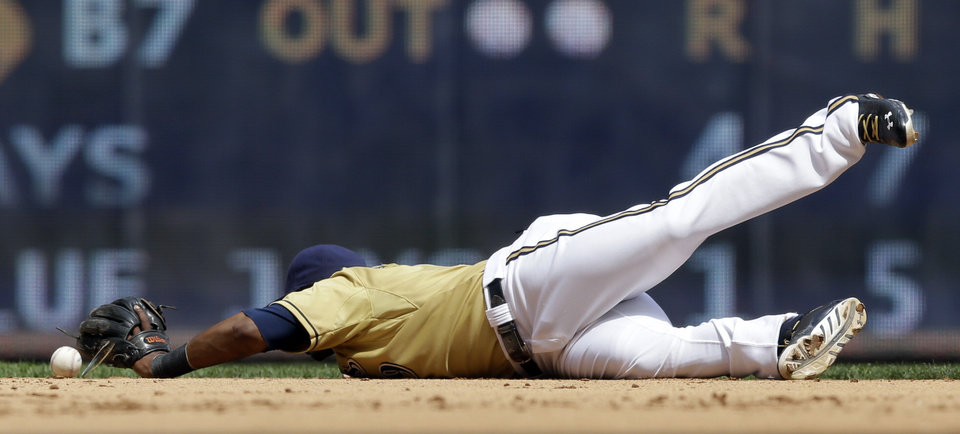 Milwaukee Brewers shortstop Jean Segura cannot come up with a ball hit by Miami Marlins' Giancarlo Stanton during the seventh inning of a baseball game on Sunday, July 21, 2013, in Milwaukee. Segura was given an error on the play. (AP Photo/Morry Gash)