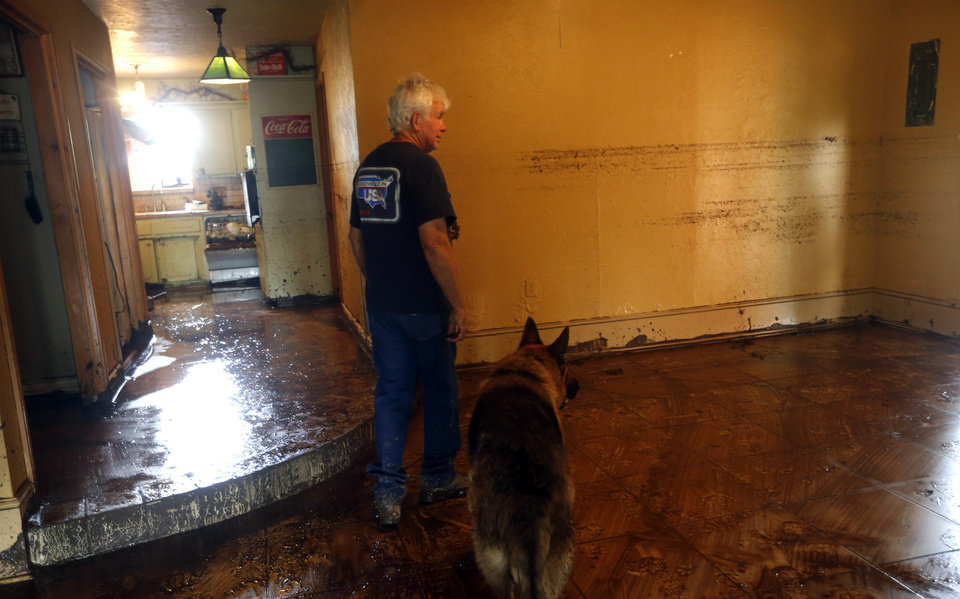 Photo - Dennis Easter and Yaffo look at damage in their home after the  West Cache Creek flooded the area in Cache, Okla., Sunday, May 24 2015. Photo by Sarah Phipps, The Oklahoman