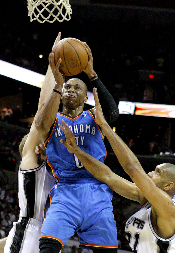 Photo - Oklahoma City's Russell Westbrook (0) goes between San Antonio's Tim Duncan (21) and Matt Bonner (15) during Game 1 of the Western Conference Finals between the Oklahoma City Thunder and the San Antonio Spurs in the NBA playoffs at the AT&T Center in San Antonio, Texas, Sunday, May 27, 2012. Oklahoma City lost 101-98. Photo by Bryan Terry, The Oklahoman
