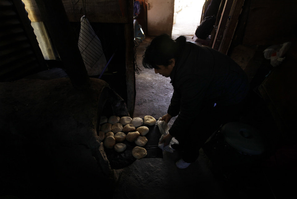 Photo - In this May 23, 2013 photo, Martina Lopez cooks bread in her home in El Corral, near the facilities of Barrick Gold Corp's Pascua-Lama mining project in northern Chile. Chile's environmental regulator blocked Barrick Gold Corp.'s $8.5 billion Pascua-Lama project on Friday, May 24, 2013, and imposed its maximum fine on the world's largest gold miner, citing