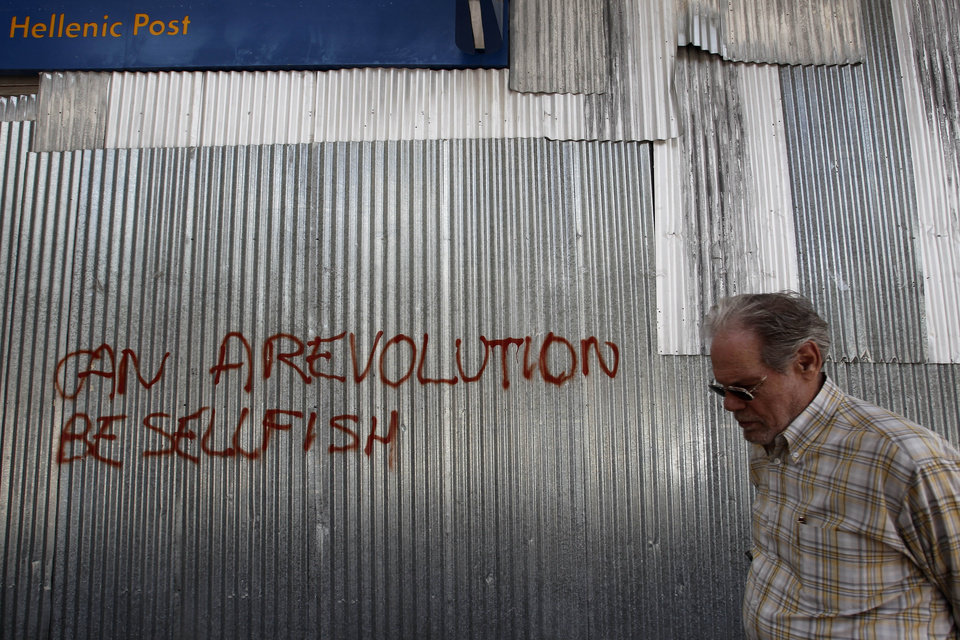 Photo -   A Greek man walks past metal sheeting sprayed with a slogan in English reading