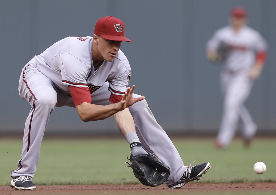 Photo - Arizona Diamondbacks shortstop Nick Ahmed fields a ground ball hit by Cincinnati Reds' Todd Frazier in the first inning of a baseball game, Monday, July 28, 2014, in Cincinnati. Ahmed threw Frazier out at first. (AP Photo/Al Behrman)