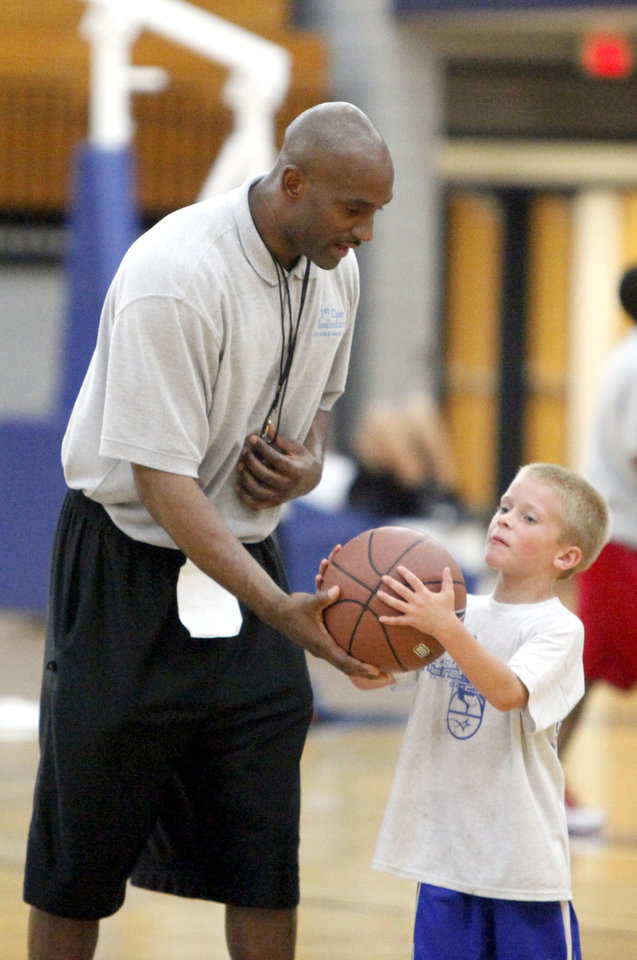 Jonathan Triplett hands the ball to Cole Riggs, 6, during the 1st Class Individual Life Skills and Basketball camp at Oklahoma City University, Thursday, July 15, 2010, in Oklahoma City. Photo by Sarah Phipps, The Oklahoman