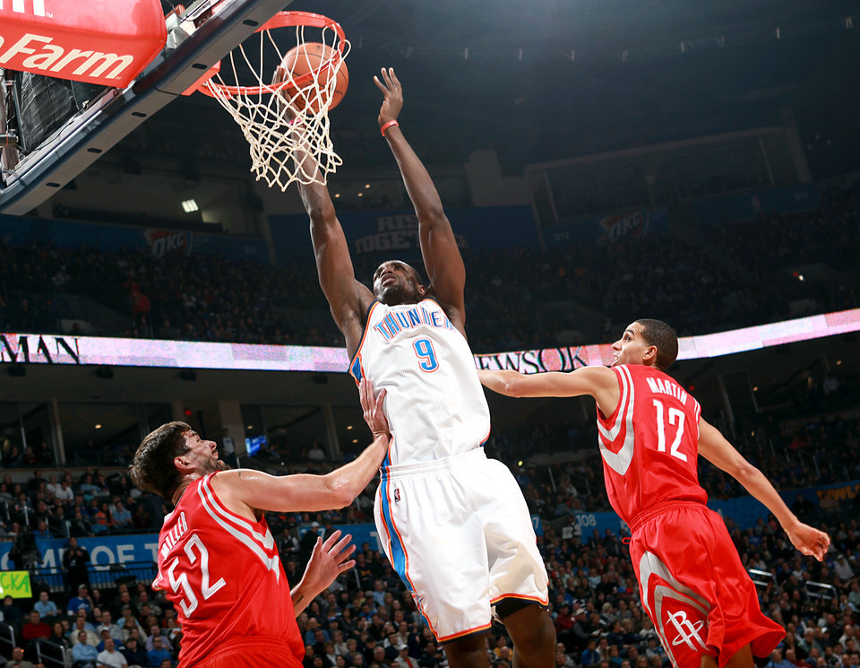 Oklahoma City's Serge Ibaka shoots in front of pressure from  Houston's Brad Miller and Kevin Martin during their NBA basketball game at the OKC Arena in downtown Oklahoma City on Wednesday, Nov. 17, 2010. Photo by John Clanton, The Oklahoman