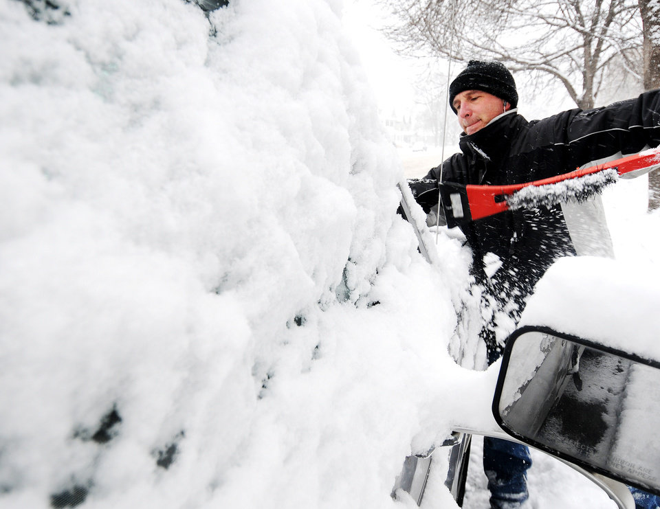 Photo - Joe Jackson clears off snow from his truck on Thursday, Dec. 20, 2012, in Winona, Minn.  The first major snowstorm of the season began its slow eastward march across the Midwest early Thursday, creating treacherous driving conditions and threatening to disrupt some of the nation's busiest airports ahead of the holiday weekend. (AP Photo/Winona Daily News, Joe Ahlquist)