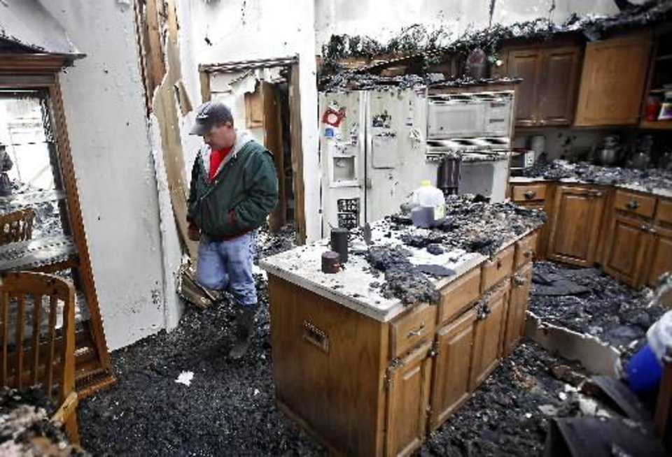 Charles Collier walks through his home as he looks over his destroyed home that was consumed by wildfires on Friday, April 10, 2009, in  Midwest  City, Okla. Photo by Chris Landsberger, The Oklahoman