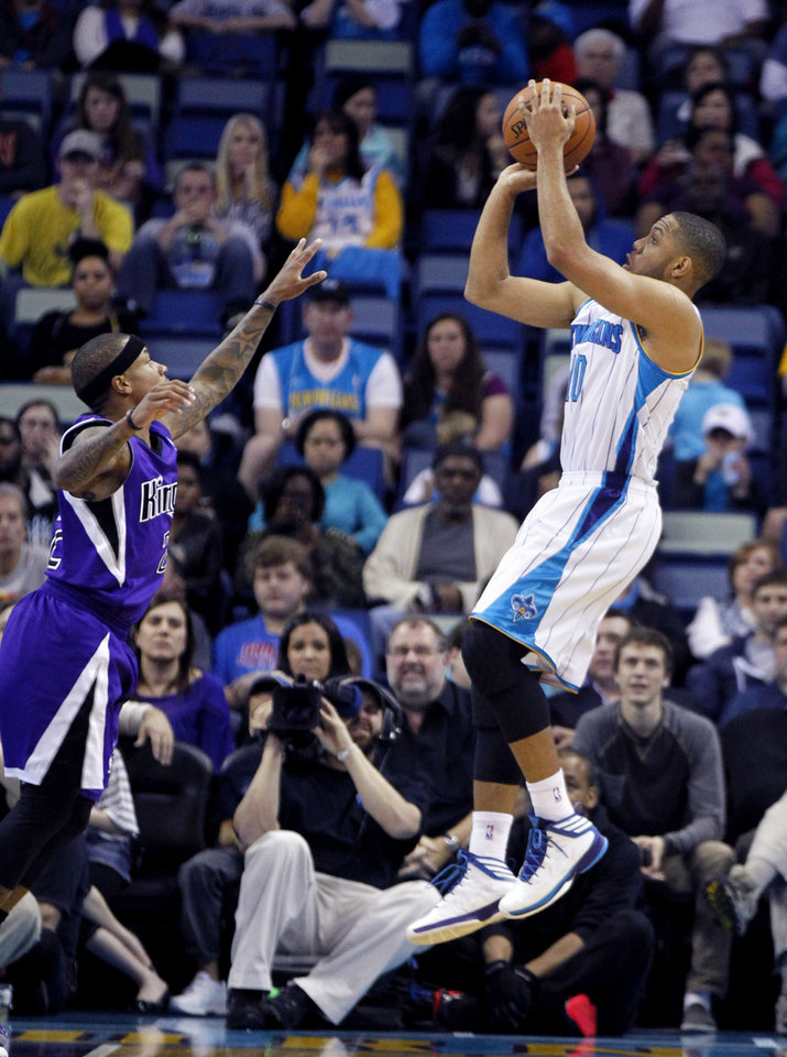 Photo - New Orleans Hornets guard Eric Gordon shoots over Sacramento Kings guard Isaiah Thomas (22) during the first half of an NBA basketball game in New Orleans, Sunday, Feb. 24, 2013. (AP Photo/Gerald Herbert)