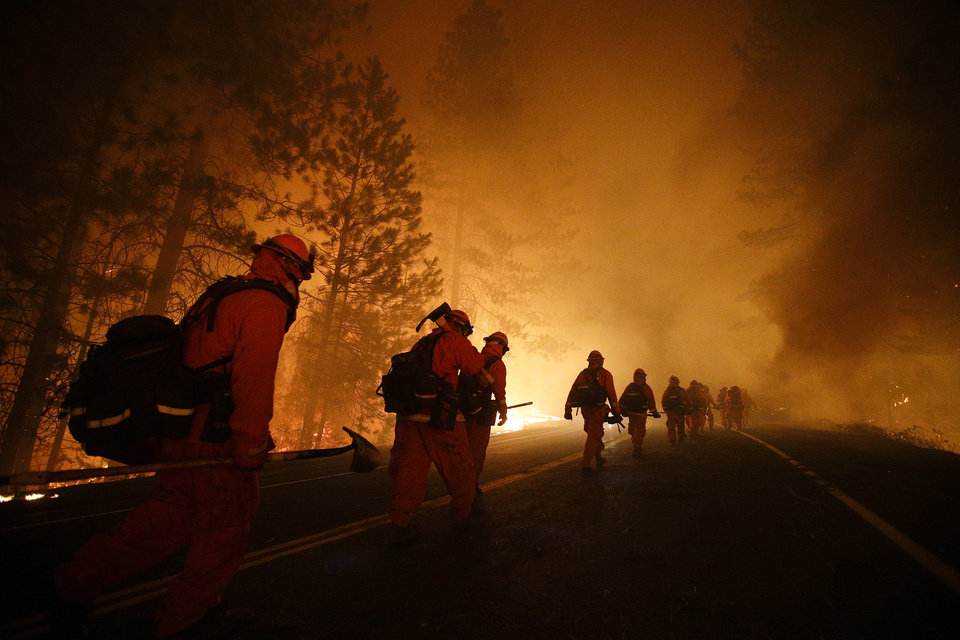 Photo - Inmate firefighters walk along Highway 120 after a burnout operation as firefighters continue to battle the Rim Fire near Yosemite National Park, Calif., on Sunday, Aug. 25, 2013. Fire crews are clearing brush and setting sprinklers to protect two groves of giant sequoias as a massive week-old wildfire rages along the remote northwest edge of Yosemite National Park. (AP Photo/Jae C. Hong)