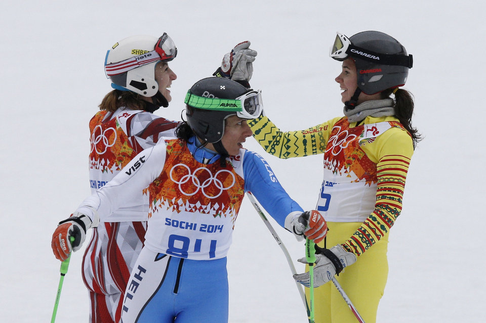 Photo - Lithuania's Ieva Januskeviciute, left, Greece's Sophia Ralli , center, and Togo's Alessia Afi Dipol, right, celebrate after completing the first run in the women's giant slalom at the Sochi 2014 Winter Olympics, Tuesday, Feb. 18, 2014, in Krasnaya Polyana, Russia. (AP Photo/Christophe Ena)