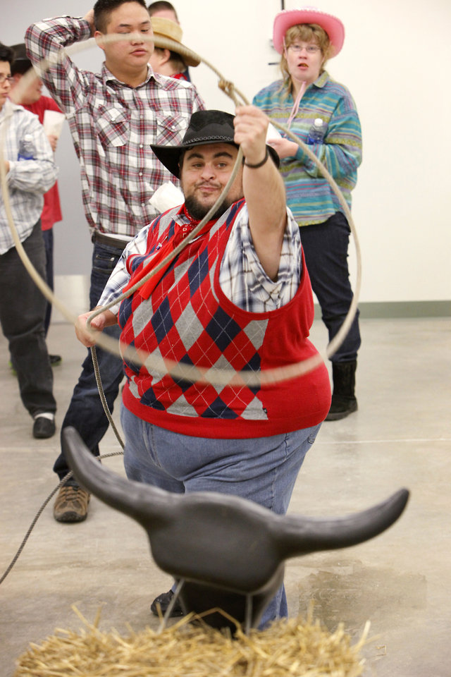 Photo - Chris Howell tries his hand at roping a practice steer during a  Dale Rogers  Center party honoring Dale Evans Rogers'  100th birthday and the opening of a new facility at NW 23 and Utah.   Photo By David McDaniel, The Oklahoman  David McDaniel - The Oklahoman