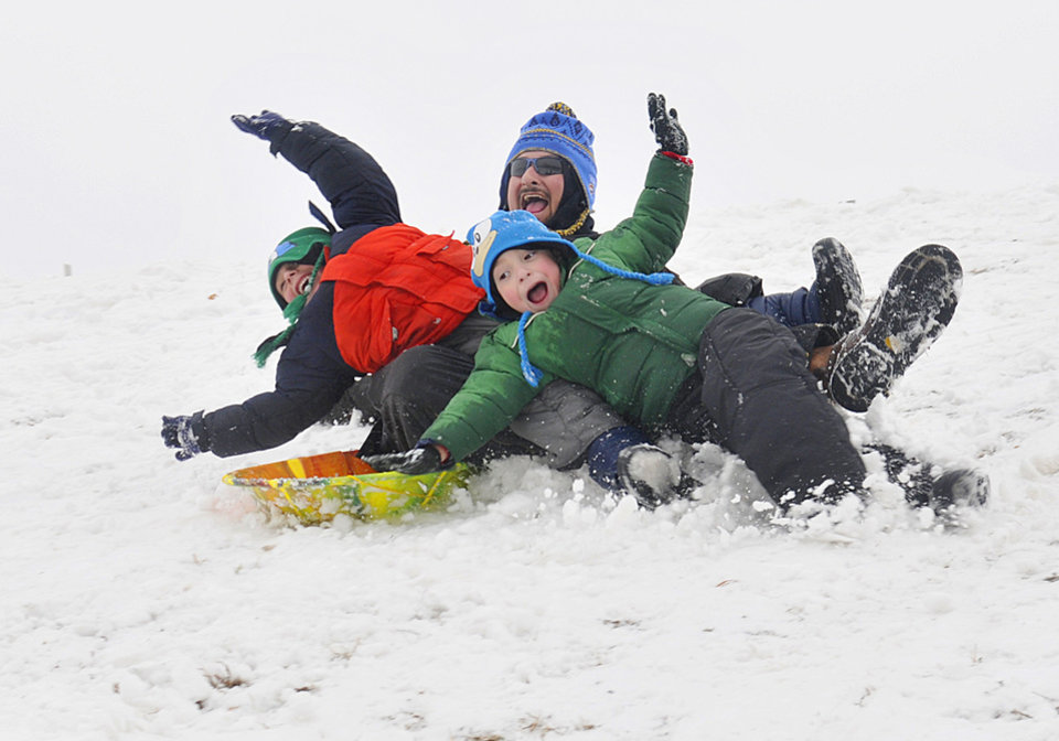 Photo - Lane Franklin sleds down an embankment with his sons, Tyson and Kyzer, Monday in Enid, Okla., Monday, Feb. 13, 2012, as  North central Oklahoma received it's first measurable snowfall of the season. (AP/Enid News & Eagle, Billy Hefton)