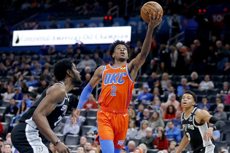 Photo - Oklahoma City's Shai Gilgeous-Alexander (2) goes to the basket between San Antonio's Chimezie Metu (7) and Keldon Johnson (3) during an NBA basketball game between the Oklahoma City Thunder and the San Antonio Spurs at Chesapeake Energy Arena in Oklahoma City, Sunday, Feb. 23, 2020. Oklahoma city won 131-103. [Bryan Terry/The Oklahoman]