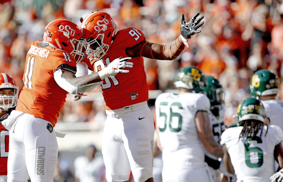Photo - Oklahoma State's Mike Scott (91) celebrates his sack on Baylor's Charlie Brewer (12) with Amen Ogbongbemiga (11) in the second quarter during the college football game between Oklahoma State University and Baylor at Boone Pickens Stadium in Stillwater, Okla., Saturday, Oct. 19, 2019. [Sarah Phipps/The Oklahoman]