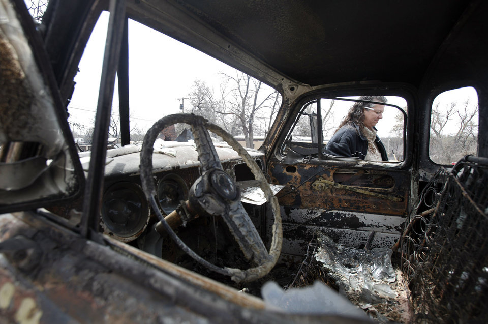 Photo - Rene Holbrook walks by the burned remains of her 1954 chevy truck that was destroyed by wildfires on Friday, April 10, 2009, in Choctaw, Okla. Holbrook's home was also destroyed by the fires.  Photo by Chris Landsberger, The Oklahoman